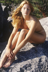 Naked young woman sitting on a rock, outdoors