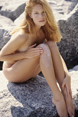 Naked young woman applying suncream on her leg, outdoors
