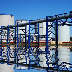 industrial pipelines and storage tanks against blue sky with ref