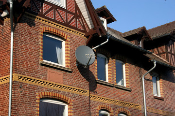 Satellite dish at an old house with brown brick stone