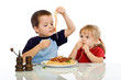 Two kids eating pasta with their hands