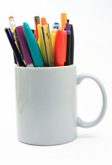 Rainbow of colored writing instruments in a coffee cup