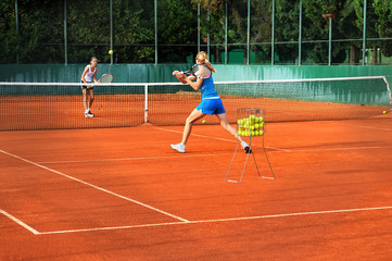 Two young women playing tennis outdoors on Two young womwn playi