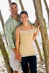Couple leaning on tree at beach