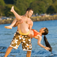 Boyfriend lifting girlfriend on beach