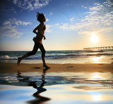 Fototapety Woman running by the ocean at sunset