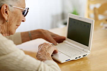 Elderly woman typing on laptop computer