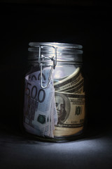 Dollar and euro banknotes inside closed glassy pot