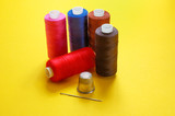 thread coils, thimble and a needle poster