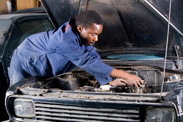 african mechanic working on a car