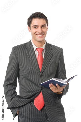 Young happy smiling businessman with organizer, isolated