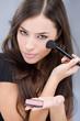young pretty girl holding powder brush
