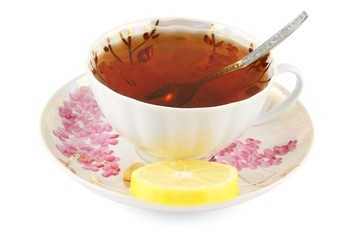Cup of tea with lemon and teaspoon on white