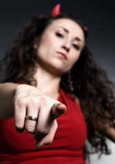 young woman with red horns pointing