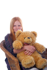 Redhead girl is sitting in the armchair with her toy bear