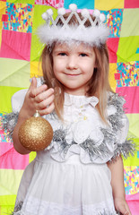 The girl in a New Year's dress with a brilliant sphere