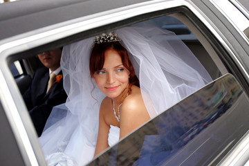 Smiling bride with groom in wedding limo