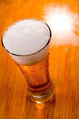 Beer glass over wooden background