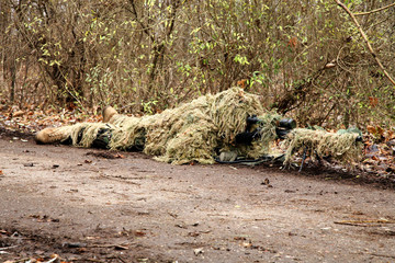 Soldier in camouflage, lies ready for the shot