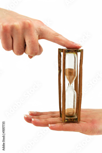 Female hand holds hourglass
