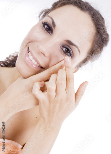 Young woman, close-up, inserting a contact lens in her eye