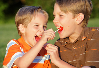 two brothers sharing lollipops