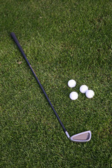 Golf-ball and golf-club on the grass