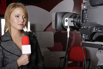 serious TV reporter in live transmission lookin at camera