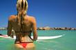 Surfer Girl in a bikini standing in the ocean next tp surfboard