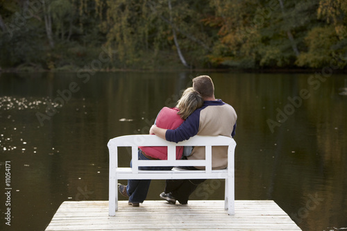 couple sitting on a bench at a lake in autum