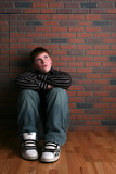 Fototapety teenage boy sitting on floor with arms on knees