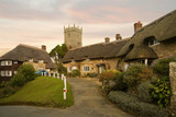 Idyllic hamlet of thatched cottages at sunset with church poster