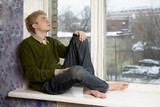 young handsome man sitting on the window-sill poster