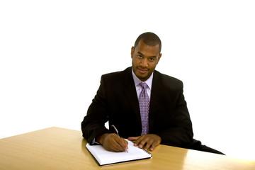 Black Man Writing at Desk Looking at Camera