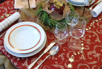 Decorative Christmas table serving. Glasses, candles, plates.