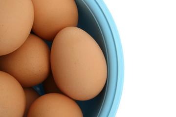 Eggs in light blue bowl isolated on white