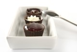 Three little chocolate cakes in a line