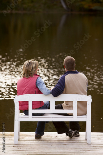 couple sitting on a bench at a lake in autumn