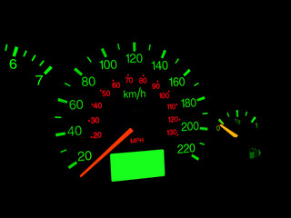 Close up of car dashboard gauges at night.