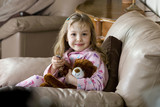 Little girl in pink pajamas with a teddy bear poster