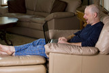 Man looking at laptop computer in pajamas poster