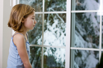 girl looking out window at snow