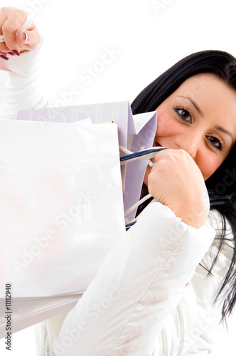 side view of smiling female carrying shopping bags on white back