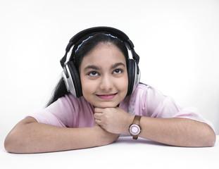 asian teenage girl of indian origin listening to music