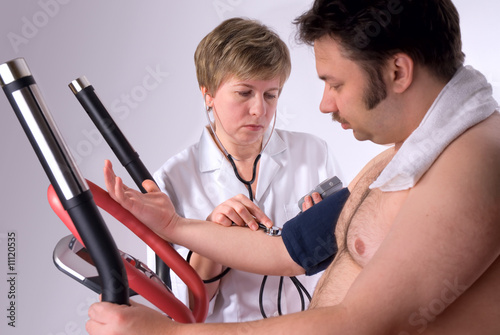 man is being observed by doctor after training
