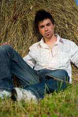 Young Man in Jeans relaxing on the hay