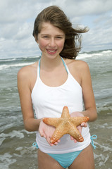 A young girl holding a starfish