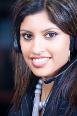 face of smiling indian business woman with headphones