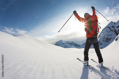 Skier reaches his arms up over a snowy mountain landscape