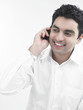 asian male talking on his cell phone with a happy expression